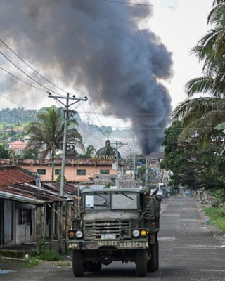 A Philippine Marines truck speeds away as black smoke billows from burning houses after military helicopters fired rockets at militant positions in Marawi on May 30, 2017. Photo by Ted Aljibe/AFP