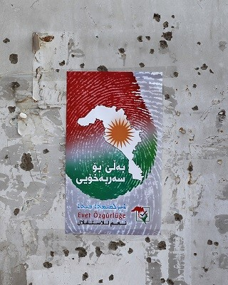 A poster encouraging people to vote in the upcoming independence referendum for the Kurdistan region is seen on a bullet-riddled wall in the Iraqi city of Kirkuk on September 24, 2017. Iraqi Kurds are preparing to vote in a referendum set for September 25 on independence for their autonomous northern region, despite warnings within the country and from neighbours Iran and Turkey. / AFP PHOTO / AHMAD AL-RUBAYE