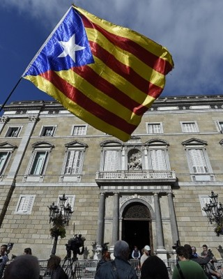 A person waves a Catalan pro-independence flag in front of the 'Generalitat' palace (Catalan government headquarters) in Barcelona on October 30, 2017. Spain enters uncharted and potentially perilous territory today as Madrid moves to take over the running of Catalonia in response to the rebellious region's parliament unilaterally declaring independence.   / AFP PHOTO / LLUIS GENE