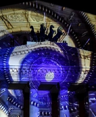 """People watch a light show projected on the facade of the Bolshoi Theatre in Moscow on September 23, 2017, during the """"Circle of Light"""" Moscow International Festival. / AFP PHOTO / Vasily MAXIMOV"""