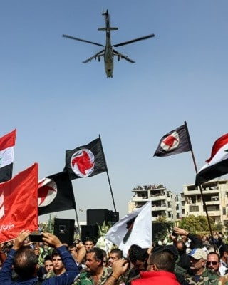 Syrians wave their national flags and those of the Syrian Social Nationalist Party in a stadium as a Russian-made Mil Mi-24 helicopter gunship hovers above during the funeral for Brigadier General Issam Zahreddine, in the southern city of Suwaida on October 20, 2017. Zahreddine, accused over the 2012 deaths of prominent US journalist Marie Colvin and French photographer Remi Ochlik, was reportedly killed by an explosion in the eastern city of Deir Ezzor on October 18, where Russian-backed regime forces are battling the Islamic State group, was reported by pro-regime media in Damascus. / AFP PHOTO / STRINGER